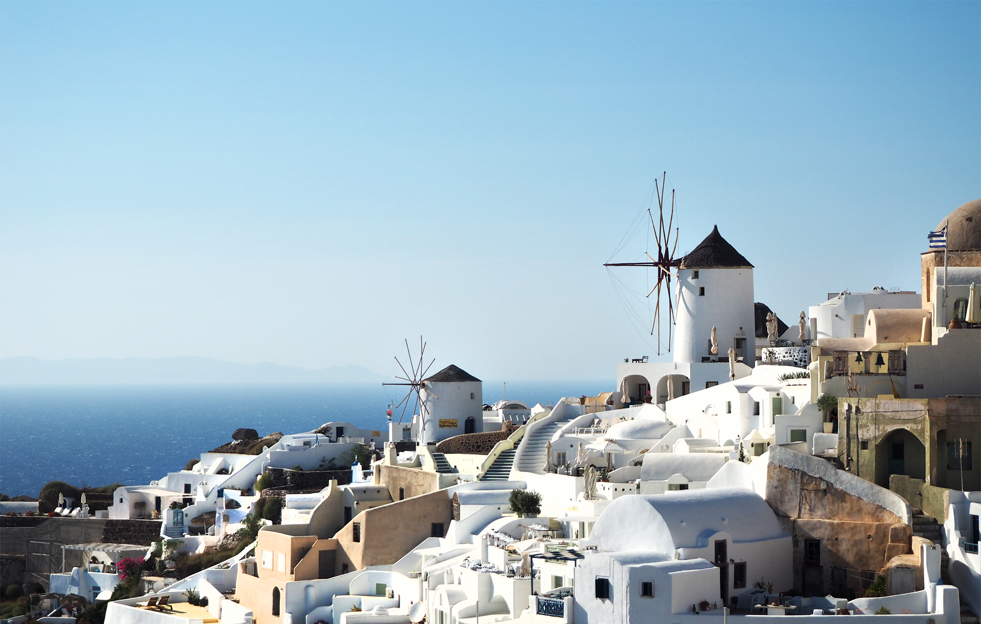 Greek Island Destination - Santorini, view of white greek architecture with windmills overlooking the caldera