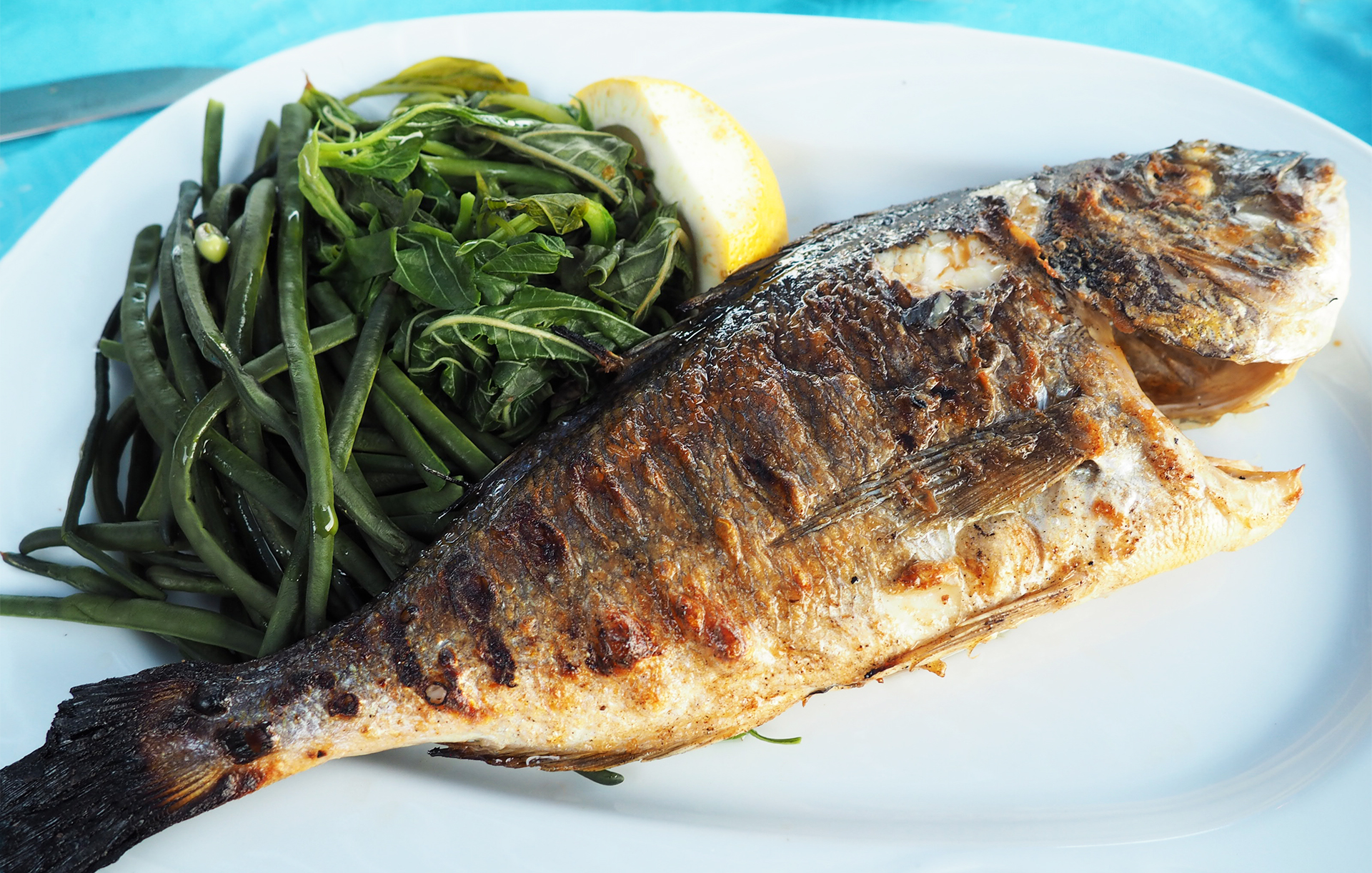 Lunch is served, a plate with freshly caught and grilled fish with locally grown green beans and a slice of fresh lemon