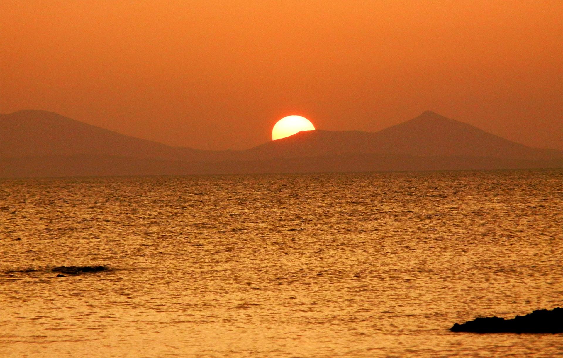 Burnt orange sunset views from Oia, greek island destination Santorini