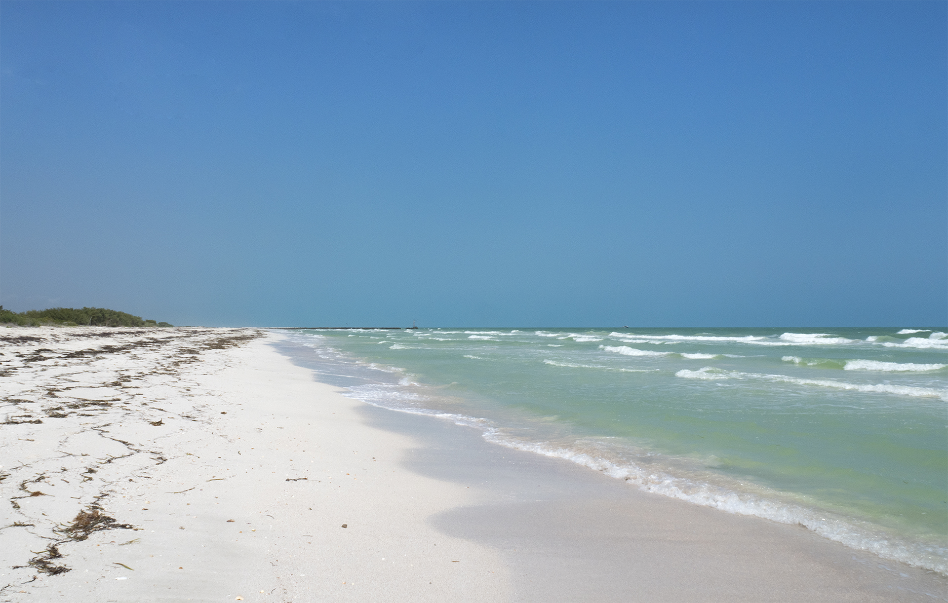 Blue sky, an endless beach of sand and the waves coming to shore from the Gulf of Mexico
