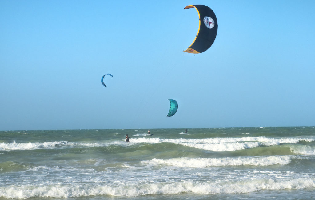 Three kite surfers riding the waves