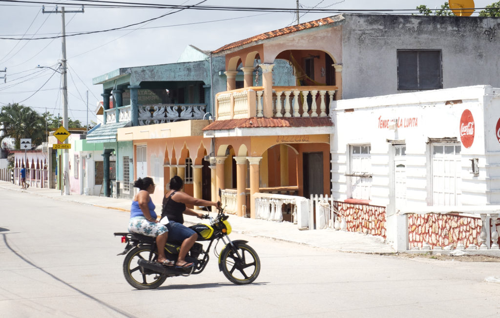 Two ladies riding a motorcycle on the main street in El Cuyo