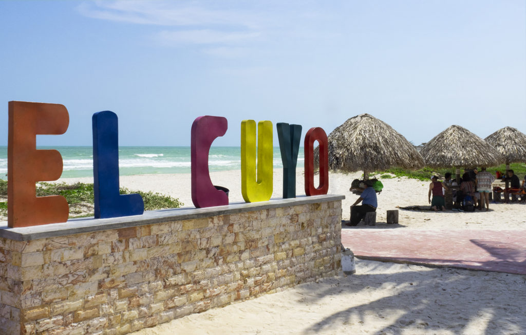 Here's the El Cuyo sign made of colourful letters. Nearby are families picnicing under the palapas
