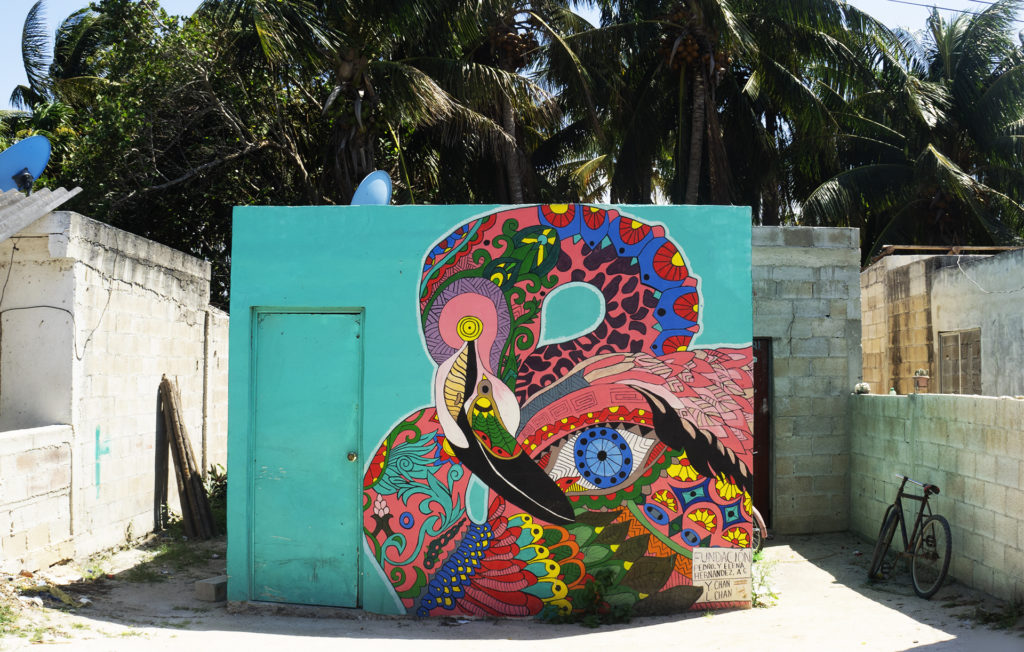 Colours and details decorate this flamingo wall art on a turquoise box house.