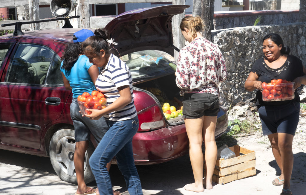 Three Mayan ladies are selling fruits and vegetables from the back of their car. Tomatos, mangoes, avocados and more