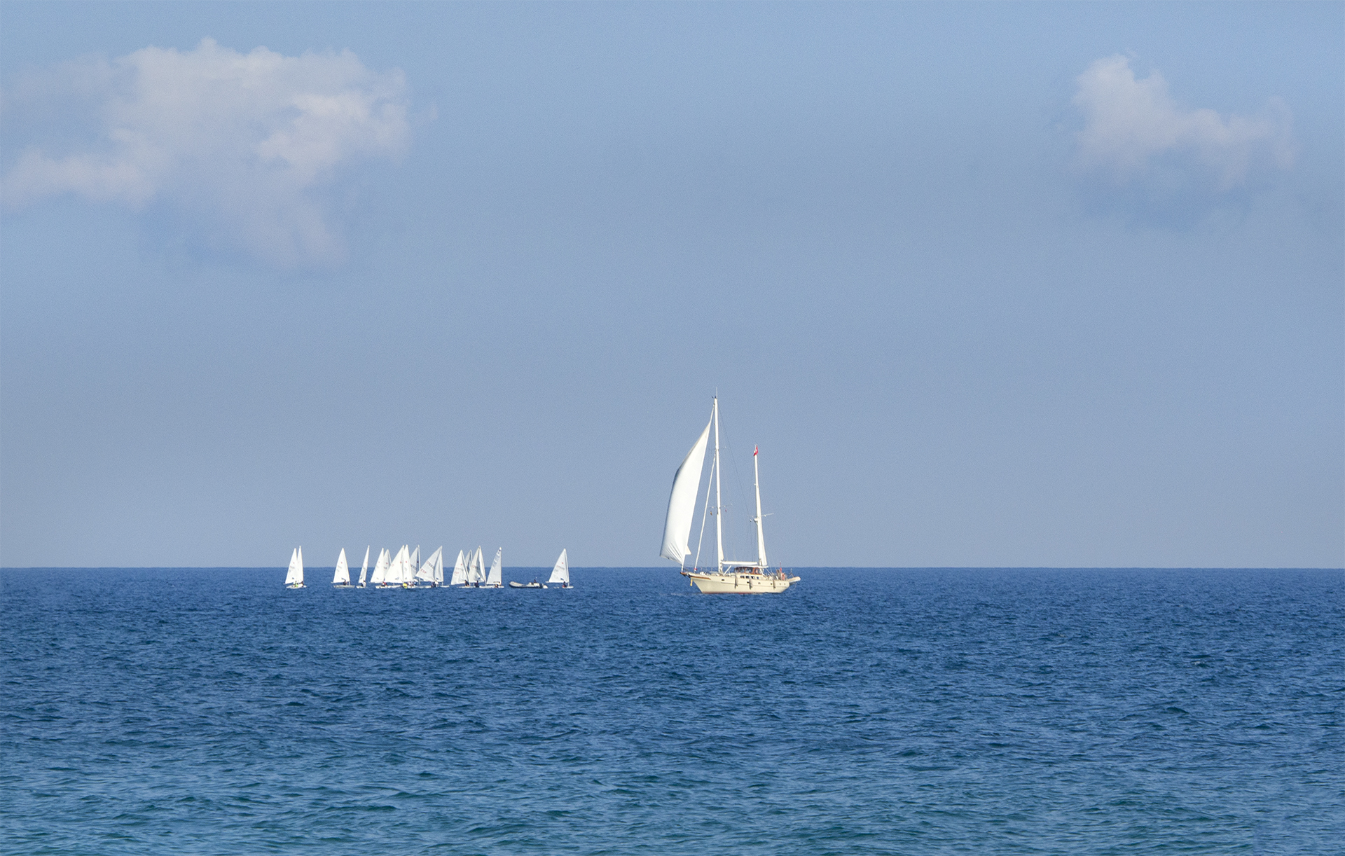 Sailing School on the Mediterranean Sea, blue sky with puffs of clouds with the blue sea and white sailboats travelling in the wind