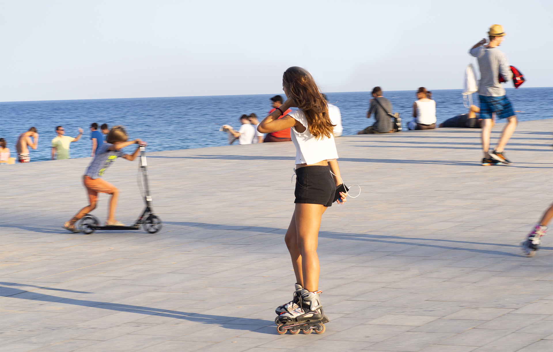 People enjoying the activities by Barceloneta Beach, rollerblading, walking, riding scooters and relaxing