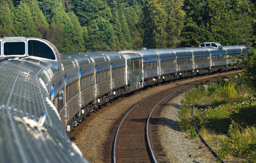 The Vancouver to Jasper Train. VIA Rail's 12+ train cars turning a corner, you can see two dome cars and a panorama car too. The stainless steel is shining bright in sunshine with the green trees as a backdrop